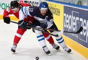 MINSK, BELARUS - MAY 16: Finland's Olli Jokinen #12 and Switzerland's Dean Kukan #34 battle for the puck during preliminary round action at the 2014 IIHF Ice Hockey World Championship. (Photo by Andre Ringuette/HHOF-IIHF Images)